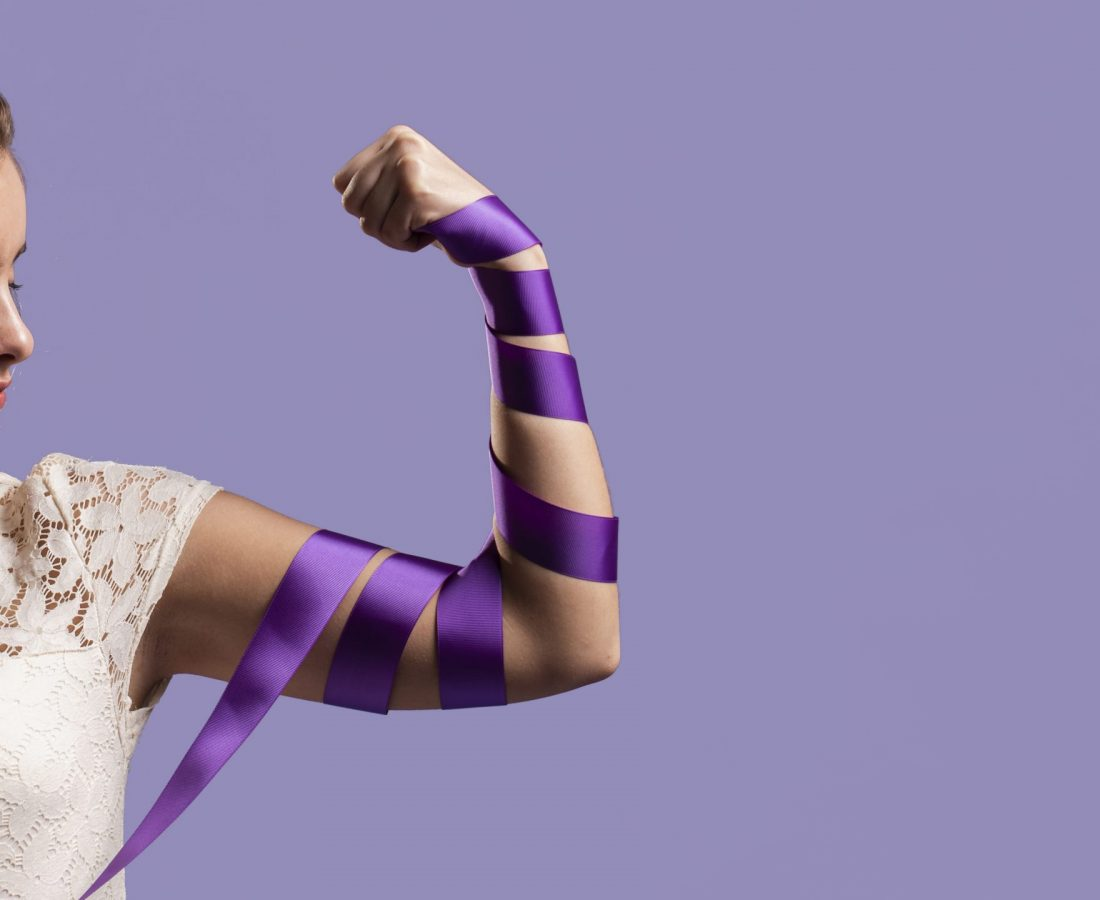 woman-flexing-her-arm-with-ribbon-and-copy-space
